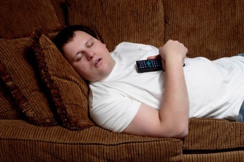 A young man sleeps on a couch, with a TV remote control firmly gripped in his hands.
