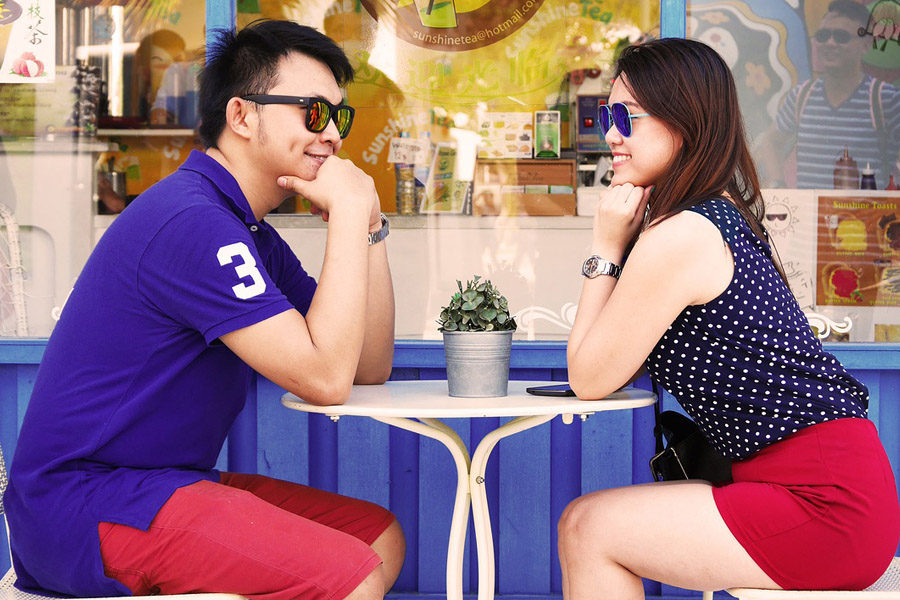 Couple wearing sunglasses while dating staring each other
