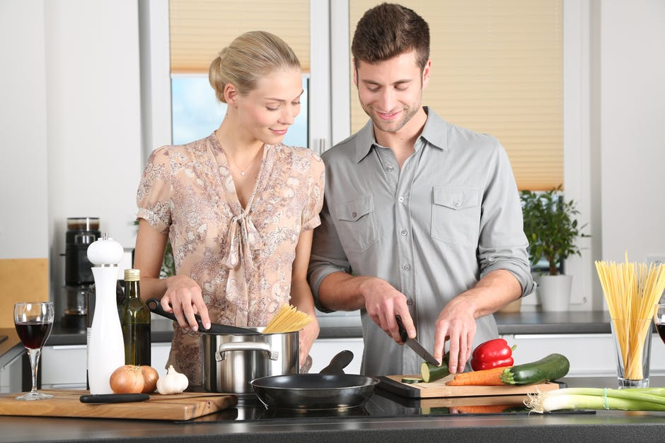 man and woman cooking together
